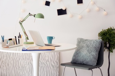 Stylish workplace with laptop on table in office