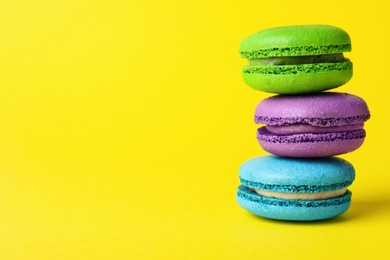 Delicious colorful macarons on yellow background, closeup, Space for text