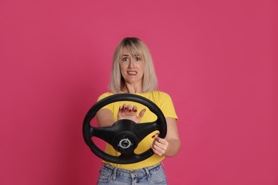 Emotional woman with steering wheel on crimson background
