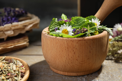 Mortar with healing herbs and pestle on wooden table