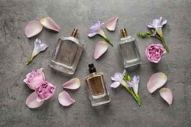 Flat lay composition of different perfume bottles, roses and freesia flowers on dark textured background