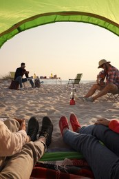 Friends resting on sandy beach, closeup. View from camping tent