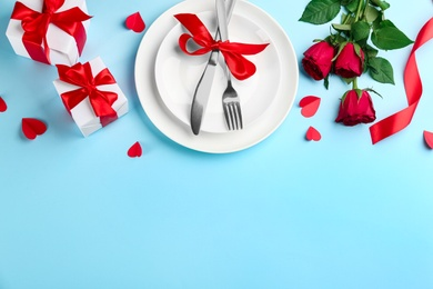 Beautiful table setting on light blue background, above view with space for text. Valentine's Day dinner