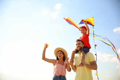 Happy parents and their child playing with kites on sunny day. Spending time in nature