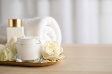 Spa composition with skin care products and flowers on wooden table. Space for text