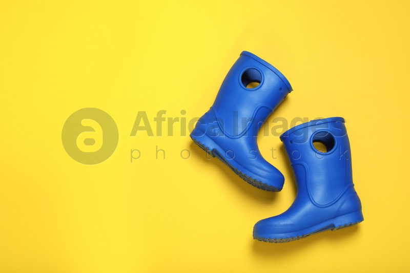 Pair of bright blue rubber boots on yellow background top view. Space for text