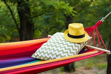 Comfortable bright hammock with soft pillow and hat at green garden, closeup