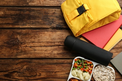 Flat lay composition with thermos and lunch box on wooden background, space for text