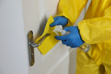 Employee in protective suit and gloves sanitizing door knob indoors, closeup. Medical disinfection