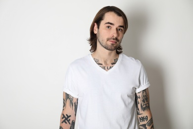 Young man with tattoos on arms against white background