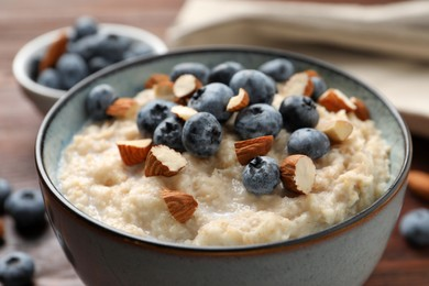 Tasty oatmeal porridge with blueberries and almond nuts on table, closeup