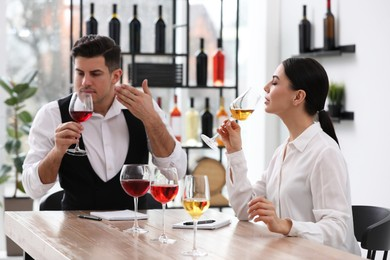 Sommeliers tasting different sorts of wine at table indoors