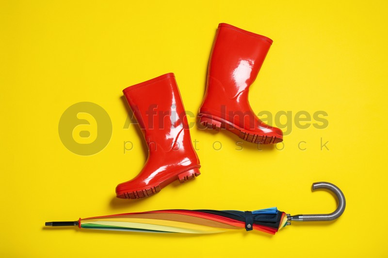 Red rubber boots near umbrella on yellow background, flat lay