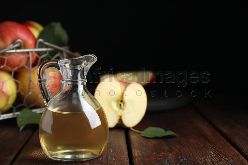 Natural apple vinegar and fresh fruits on wooden table. Space for text