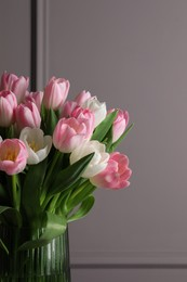 Beautiful bouquet of tulips in glass vase against grey wall