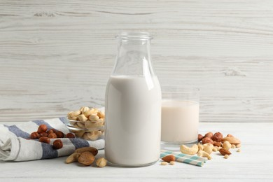 Different nut milks on white wooden table