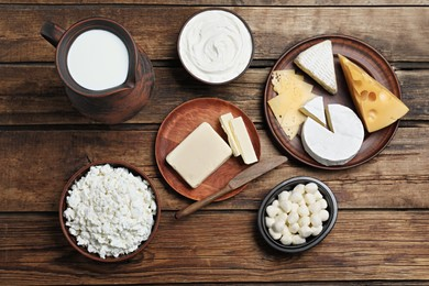Flat lay composition with dairy products and clay dishware on wooden table