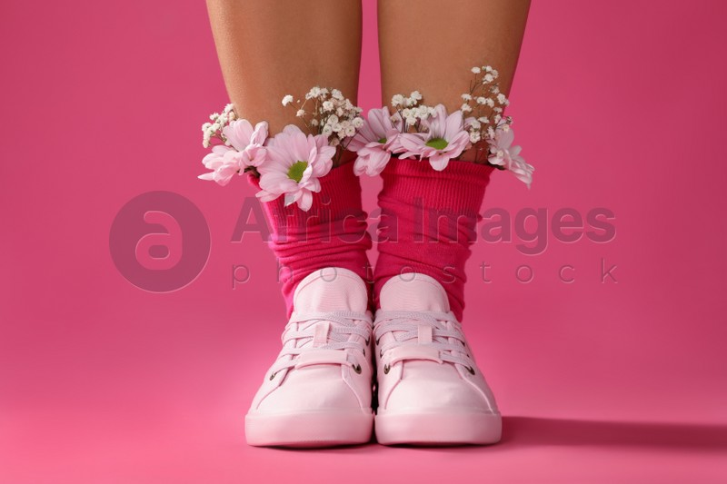 Woman with beautiful tender flowers in socks on pink background, closeup