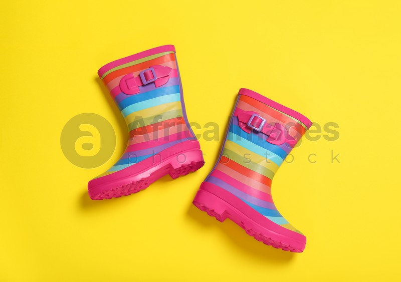 Pair of striped rubber boots on yellow background, top view