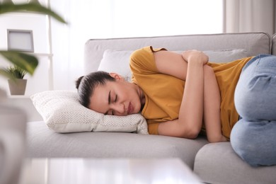 Young woman suffering from stomach ache at home. Food poisoning