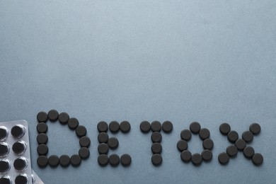 Word Detox made of activated charcoal pills near blisters on grey background, flat lay with space for text. Potent sorbent