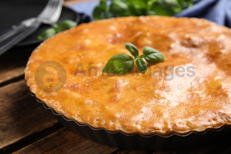 Delicious pie with meat and basil on wooden table, closeup