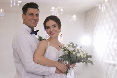 Happy newlywed couple together in festive hall