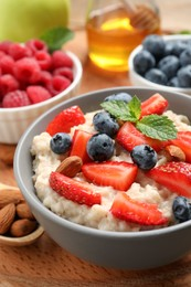 Tasty oatmeal porridge with berries and almond nuts in bowl served on wooden board