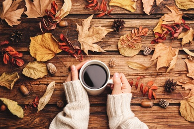 Woman with cup of hot drink at wooden table, top view. Cozy autumn atmosphere
