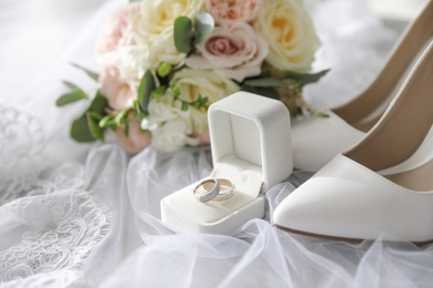 Pair of white high heel shoes, rings and wedding bouquet on lace veil