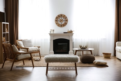 Elegant artificial fireplace and armchairs in room. Interior design