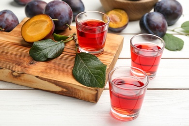 Delicious plum liquor and ripe fruits on white wooden table. Homemade strong alcoholic beverage