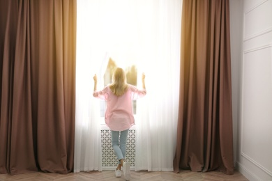 Young woman opening window curtains at home, back view