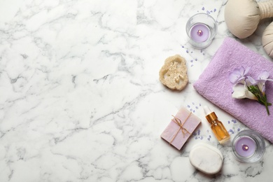 Flat lay spa composition with skin care products on white marble table, space for text