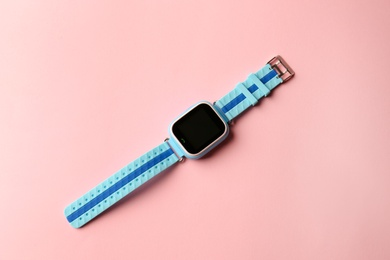 Trendy smart watch for kids on pink background, top view