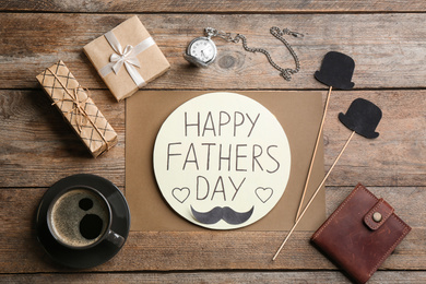 Greeting card with phrase HAPPY FATHER'S DAY, coffee and wallet on wooden table, flat lay