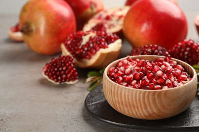 Delicious ripe pomegranate kernels in bowl on grey table. Space for text