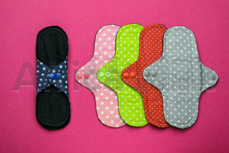 Many reusable cloth menstrual pads on pink background, flat lay