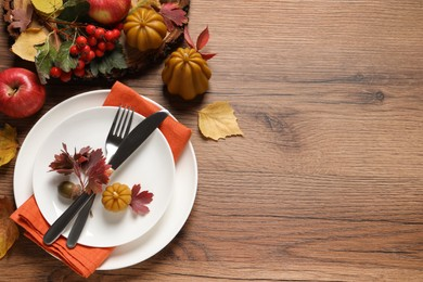 Festive table setting with autumn decor on wooden background, flat lay. Space for text