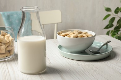 Tasty corn pads with milk served for breakfast on white wooden table in kitchen