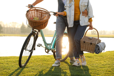 Young couple with bicycle and picnic basket near lake on sunny day, closeup