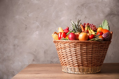 Assortment of fresh organic fruits and vegetables in basket on wooden table. Space for text