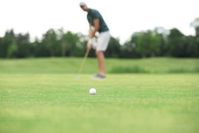 Man playing golf on green course, ball in focus. Sport and leisure