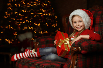Cute little child with Christmas gift sitting in armchair at home