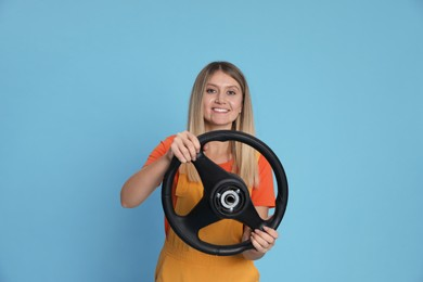 Happy young woman with steering wheel on light blue background