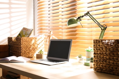 Comfortable workplace with laptop near window at home
