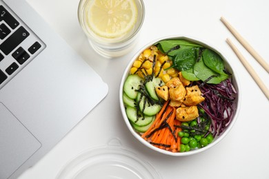 Delicious salad with chicken and vegetables near laptop on white table, flat lay