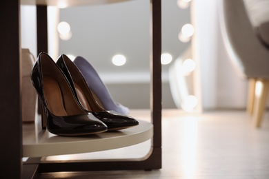 Stylish women's shoes on rack in modern boutique. Space for text