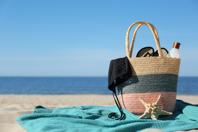 Stylish beach accessories for summer vacation on sand near sea. Space for text