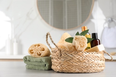 Natural loofah sponges, personal hygiene products and towel on table indoors